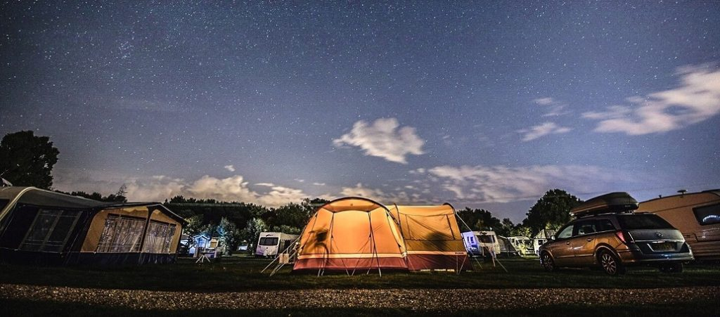 Motorhome with tent at night